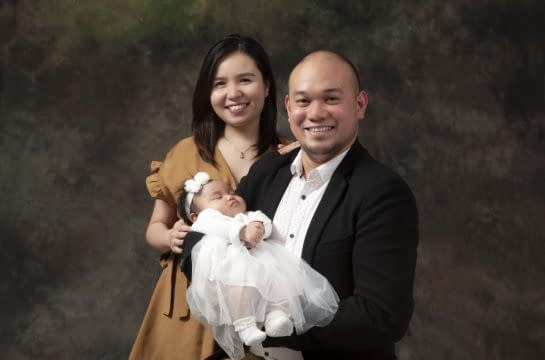 Family photo of Mother and Father with newborn baby taken at moments in time photography studio Halifax